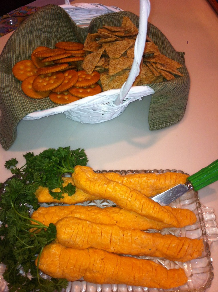 Cheeseball shaped into carrots and served with assorted crackers